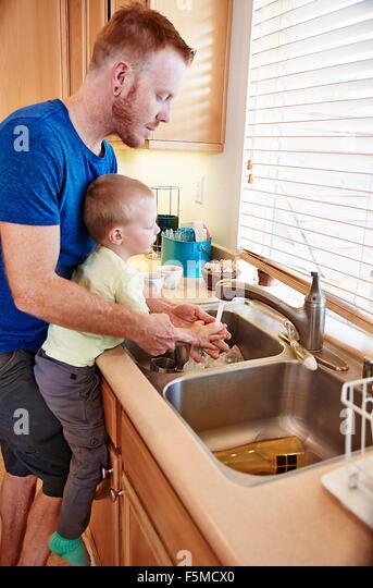 Father washing son's hands in kitchen sink - Stock-Bilder