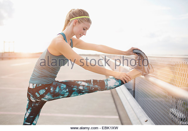 Young woman stretching leg - Stock Image