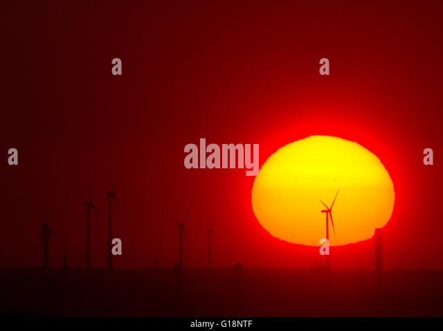 Berlin, Germany. 11th May, 2016. The sun rises behind wind turbines near the Pankow motorway junction, as seen from - Stock Image