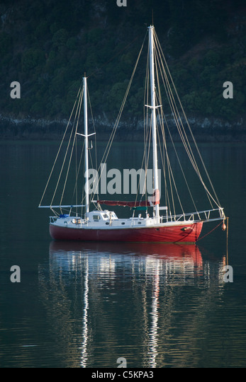 Small red yachy at anchor, Lake Wanaka, New Zealand - Stock Image