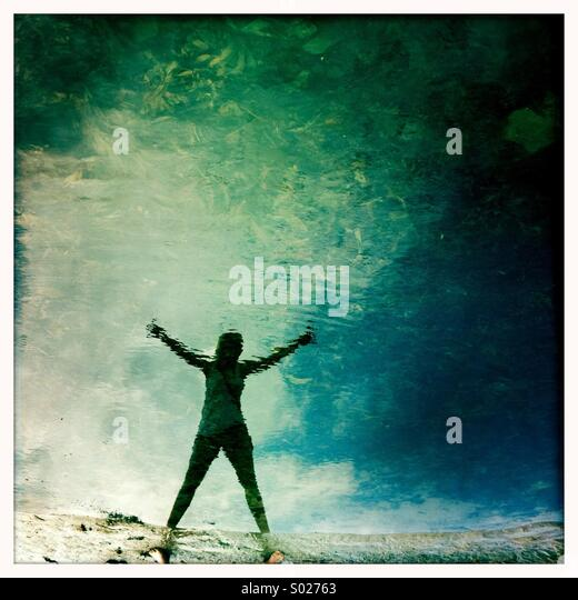 Girl's reflection in rock pool - Stock Image