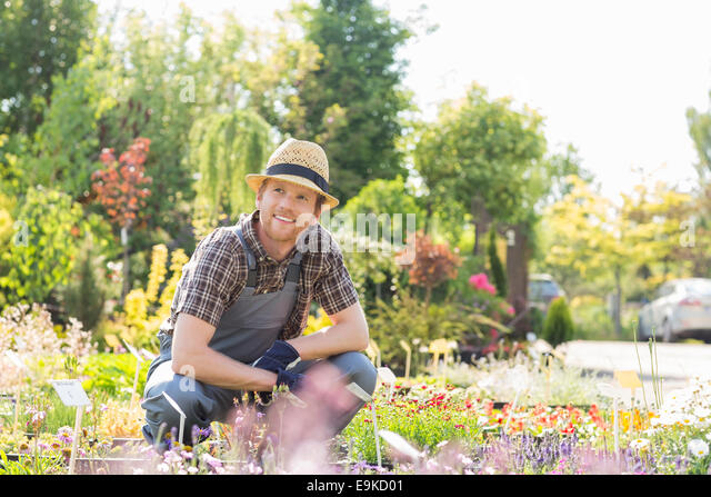 Man looking away while gardening at plant nursery - Stock Image