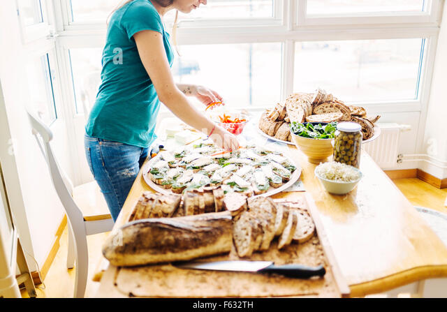 Side view of woman preparing open faced sandwich at table - Stock Image