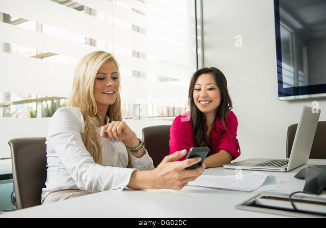 Young businesswomen looking at smartphone in conference room - Stock Image