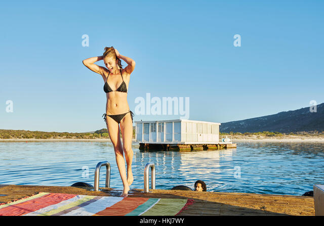 Young woman in bathing suit on sunny summer dock - Stock-Bilder