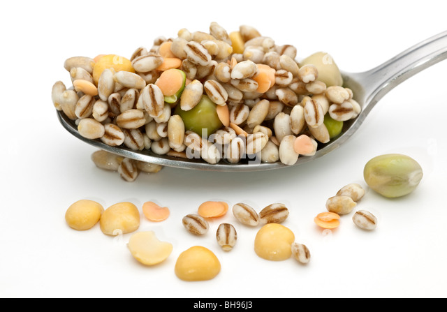 Spoonful of soaked mixed dried peas and lentils - Stock Image