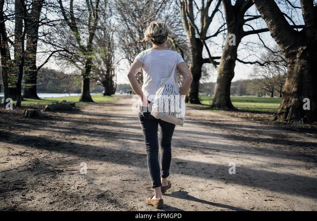 Germany, Cologne, single woman walking at city park - Stock Image
