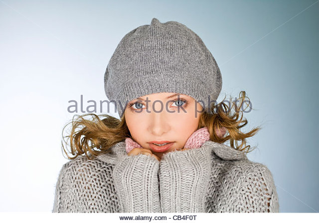 A young woman wearing a grey woollen hat, keeping warm - Stock Image