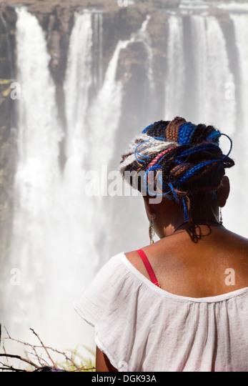 A local Zimbabwe girl sitting looking at the Victoria Falls, Zimbabwe, Africa - Stock Image