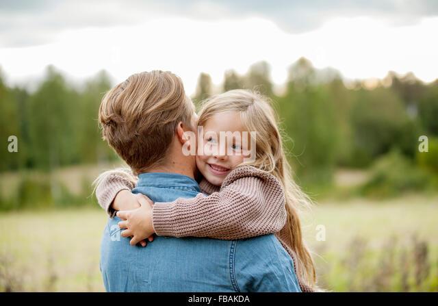 Finland, Uusimaa, Raasepori, Karjaa, Young girl (6-7) hugging her father - Stock Image