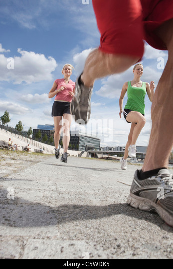 Germany, Berlin, Young people jogging together - Stock Image