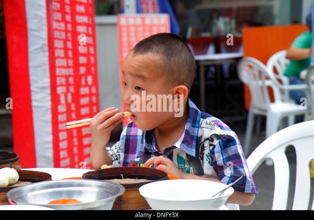 Beijing China Chaoyang District restaurant alfresco Asian boy eating using chopsticks - Stock Image