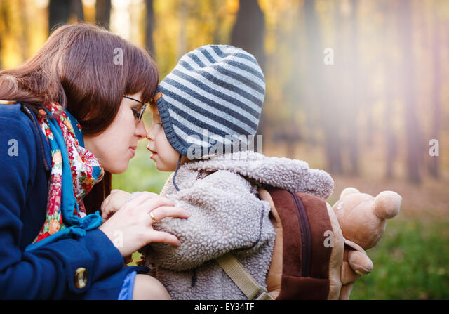 Young Happy Mother Talking to Son while Walking in the Park at the Day. Close up Portrait of Family. Copy Space - Stock Image