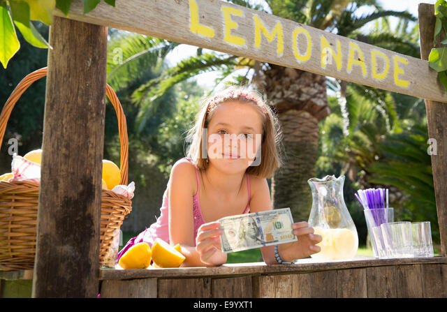 Portrait of girl on lemonade stand holding up one hundred dollar bill - Stock Image
