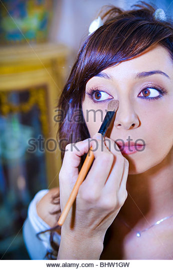 Makeup artist applying eyeshadow on a young woman with eyes open - Stock Image
