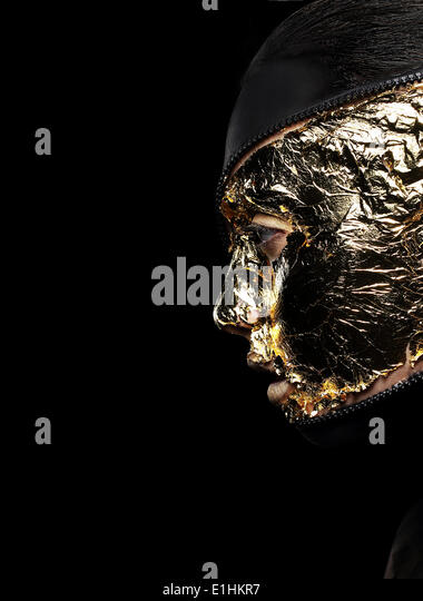 Styled Woman's Face Covered Golden Foil over Black Background. Mystery - Stock Image