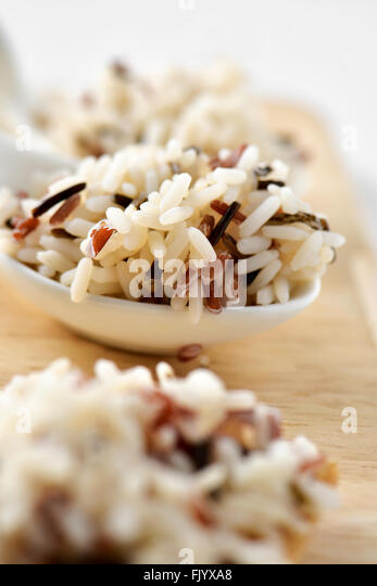 closeup of some small white ceramic bowls with cooked wild rice on a wooden surface - Stock Image