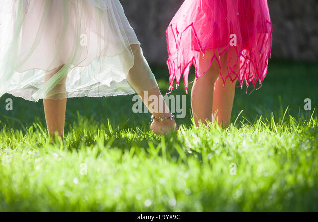 Cropped shot of the legs of two girls in fairy costume in garden - Stock Image