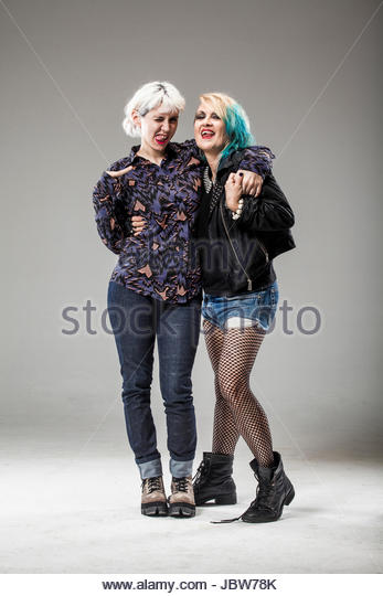Studio portrait of senior woman wearing punk clothes, hugging mid adult woman with white hair, smiling - Stock-Bilder
