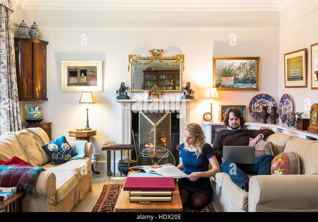 Caucasian couple hanging out in livingroom - Stock Image