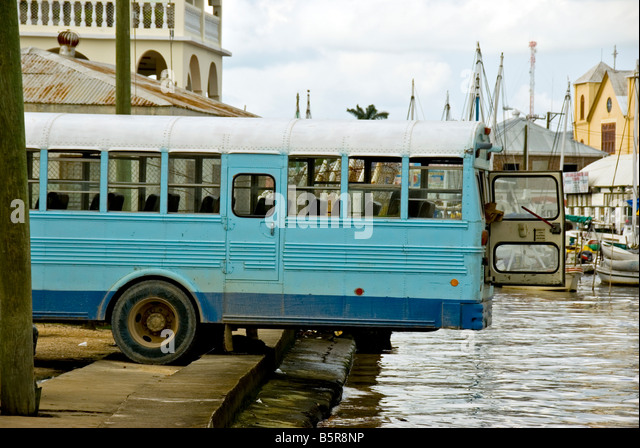 Belize City humor bus backed over river for better air flow in precarious situation - Stock Image