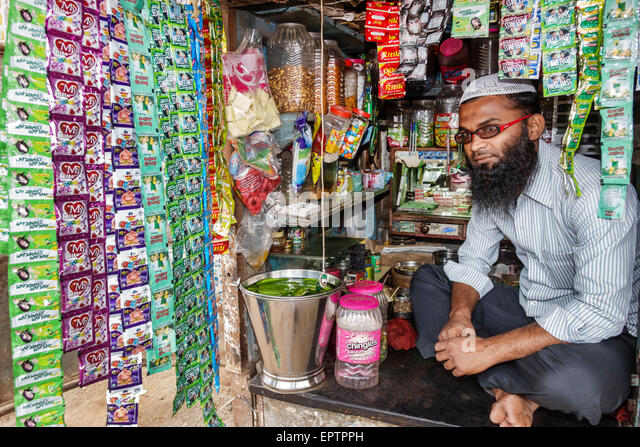 Mumbai India Asian Dharavi 60 Feet Road slum low income poor poverty man Muslim convenience store stall business - Stock Image