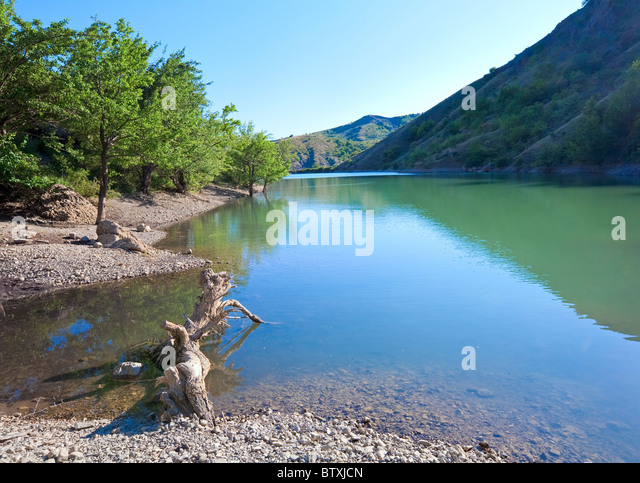 beautiful lake and summer rocks mountain behind (Zelenogorye village, Crimea, Ukraine) - Stock Image