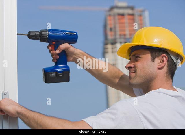 Construction worker using cordless drill - Stock-Bilder