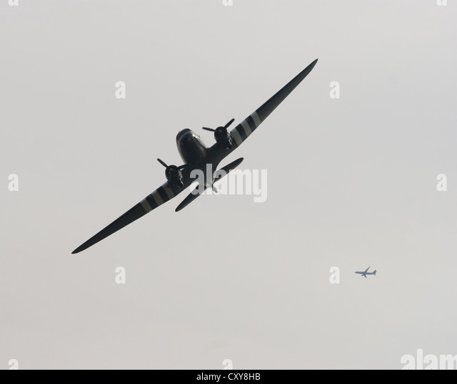 Douglas C-47 Skytrain with D-Day markings and a model day airliner in the background - Stock Image