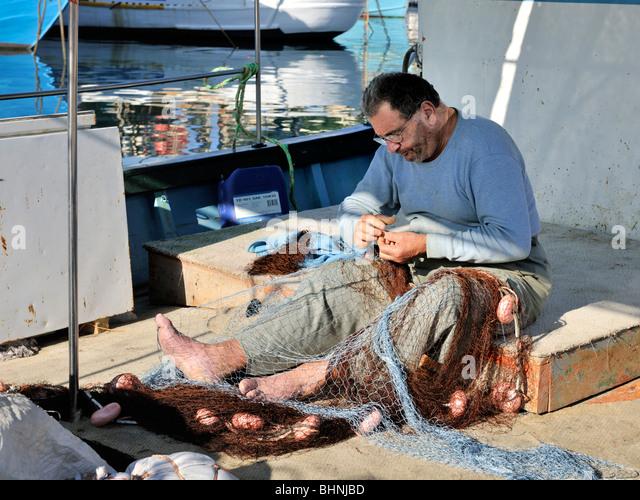 Maltese man mending fishing net, Gozo - Stock-Bilder