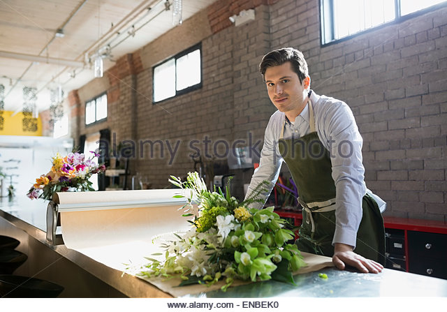 Portrait florist arranging bouquet craft paper flower shop - Stock Image
