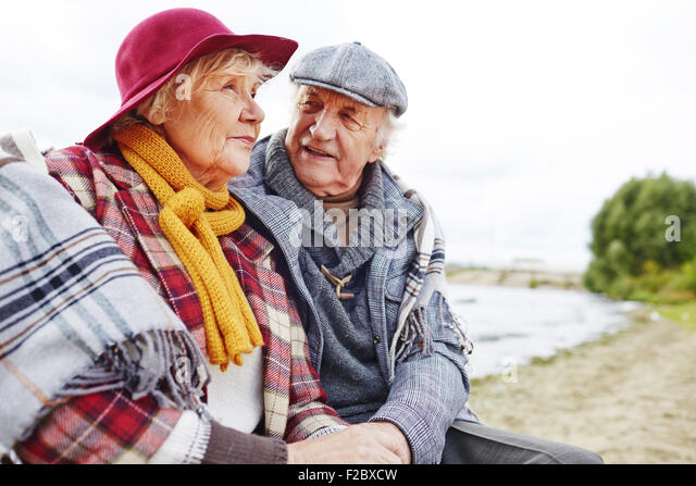 Retired couple in warm clothes having outdoor rest - Stock Image