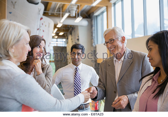 Business people exchanging business cards in office lobby - Stock Image
