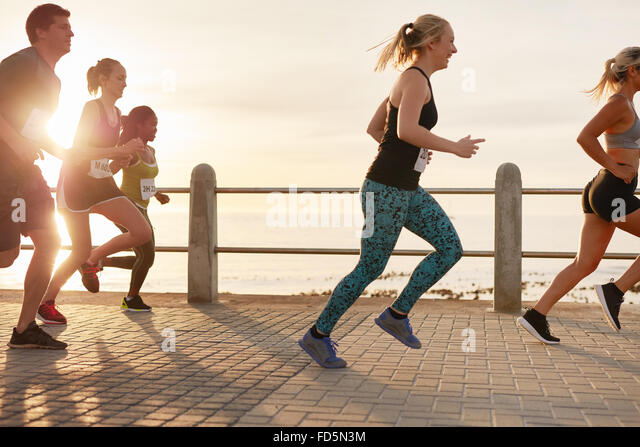 Portrait of young people running on seaside promenade. Men and women running marathon on road by the sea at sunset. - Stock Image