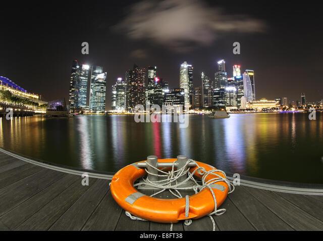 City skyline at night with lifebelt on dock, Marina Bay, Singapore - Stock Image