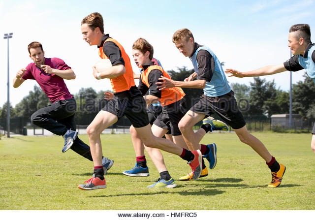 Middle schoolboys and teacher running playing rugby on field in physical education class - Stock-Bilder