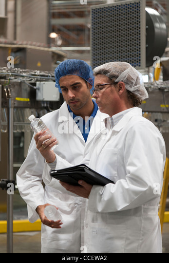 Factory workers inspecting bottled water at bottling plant - Stock Image