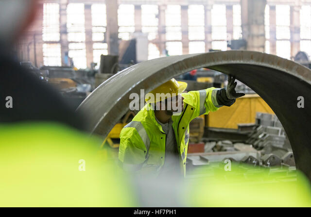 Steel worker examining pipe in factory - Stock Image