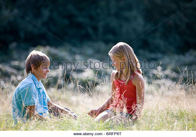A young boy and girl sitting in long grass - Stock Image