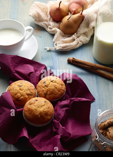 Muffins, pears, and milk on table - Stock Image