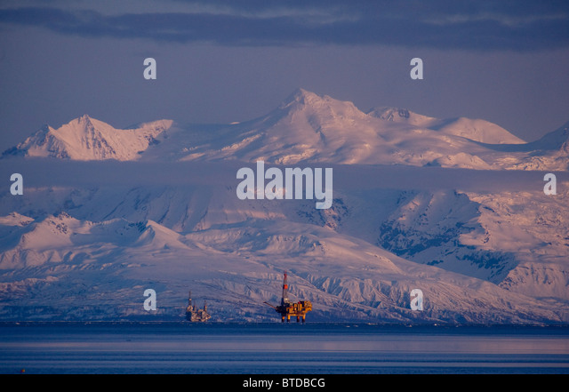 Three drill rigs in Cook Inlet with Mt. Spurr looming large in the background at sunset, Southcentral Alaska, Winter - Stock Image