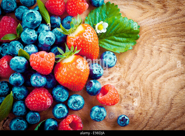 Overhead view of mixed ripe autumn berries including strawberries, raspberries and blueberries on a decorative woodgrain - Stock Image