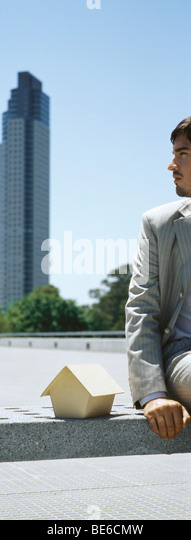 Man contemplating skyscraper in distance, miniature wooden model house at side - Stock Image