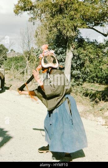 A performer dressed as a traditional character, with a complex face mask, performs at the side of a road, 1952. - Stock Image