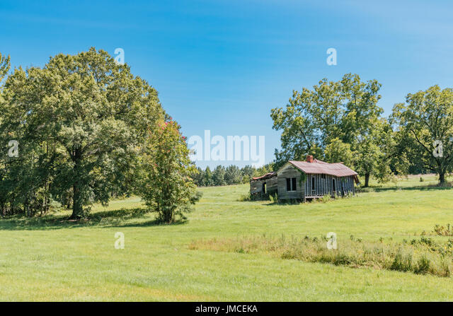 Old abandoned farm house and out building on a rural farm in central Alabama, USA. - Stock Image