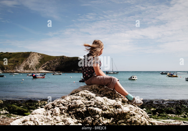 girl sitting on a rock at Lulworth Cove,UK - Stock-Bilder