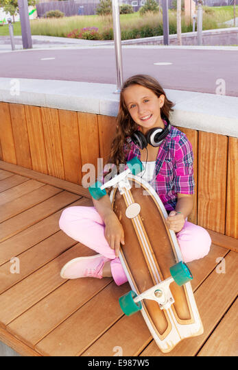 Positive girl holds skateboard while sitting - Stock Image