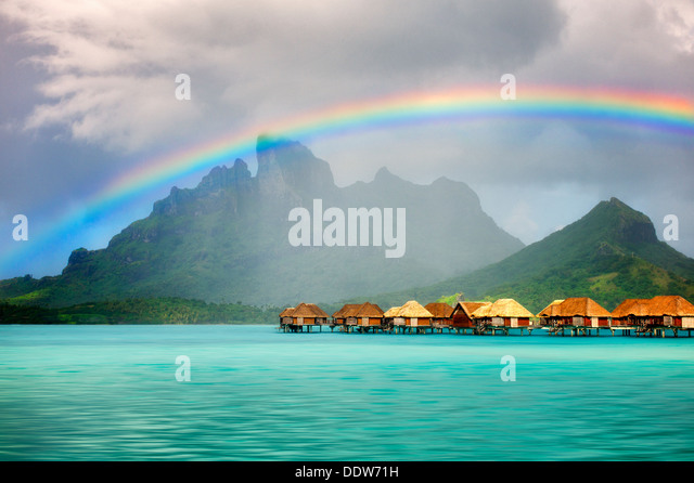 Bungalows over water with rainbow and Mt. Otemanu. Bora Bora. French Polynesia - Stock Image