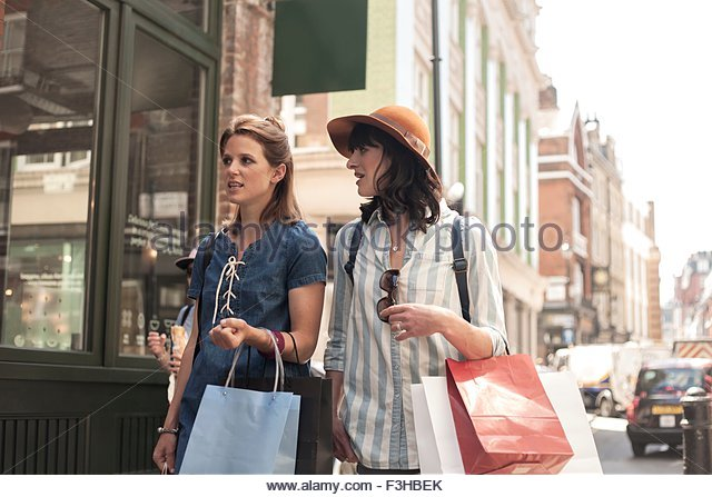 Two women carrying shopping bags looking at shop window - Stock-Bilder