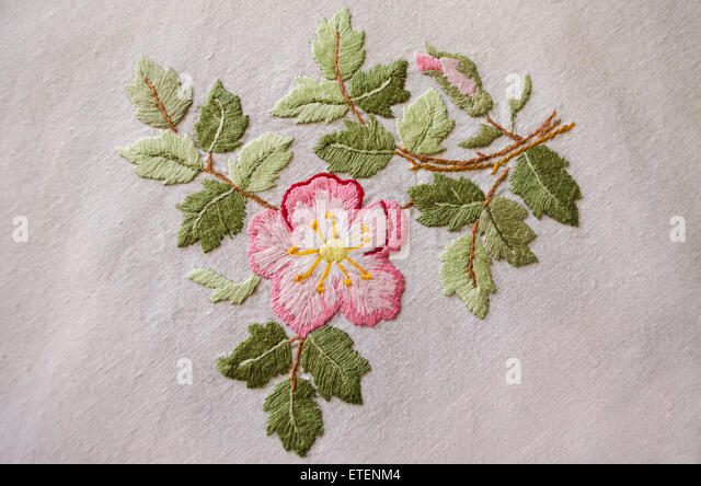 Embroidered satin stitch pink flower on cotton cloth - Stock Image